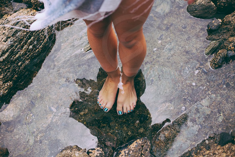 woman in white dress and blue pedicure standing barefooted in shallow water in beach photo