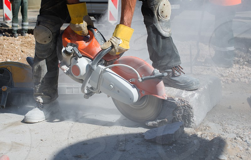 Builder worker with cut-off machine power tool breaking concrete at road construction site photo