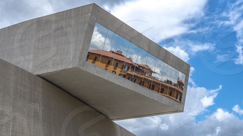 gray concrete building with mounted mirror on top reflecting brown concrete building during daytime photo
