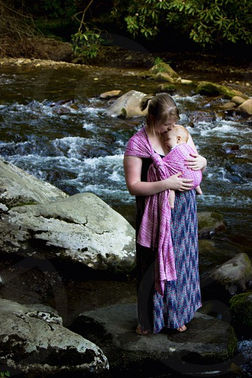 woman wearing blue dress carrying baby in pink wrap-around carrier standing on rock photo