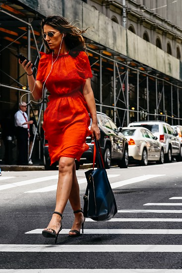 Unidentified elegant young woman in red dress watching her smartphone and with headphones crossing street in Financial District photo