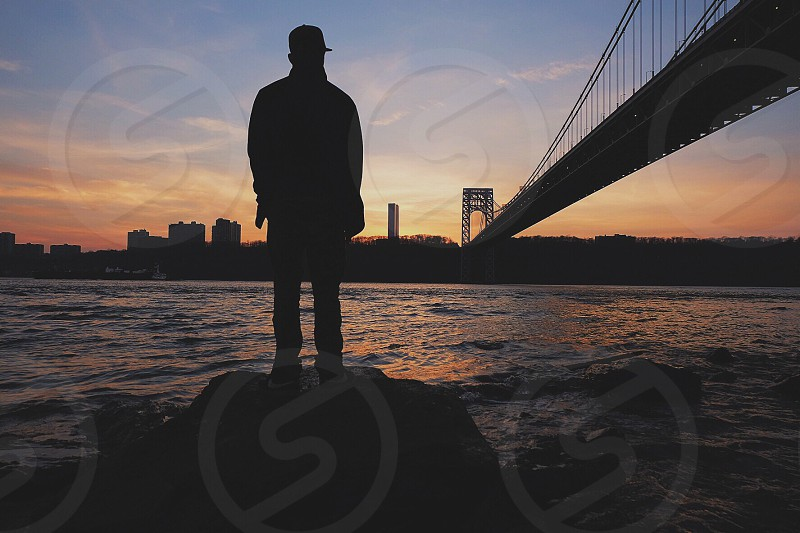 man's silhouette standing on rock photo