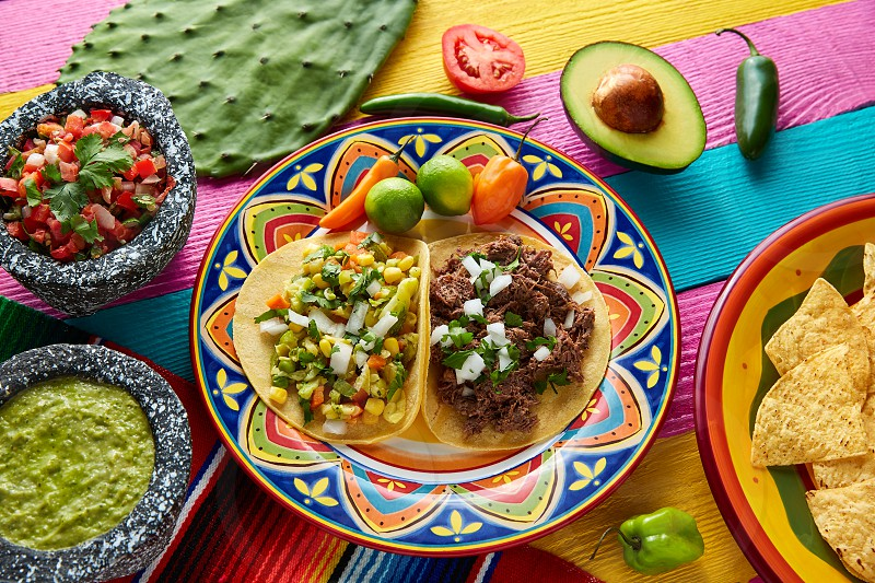 Mexican platillo tacos of barbacoa and vegetarian with sauces and colorful table photo