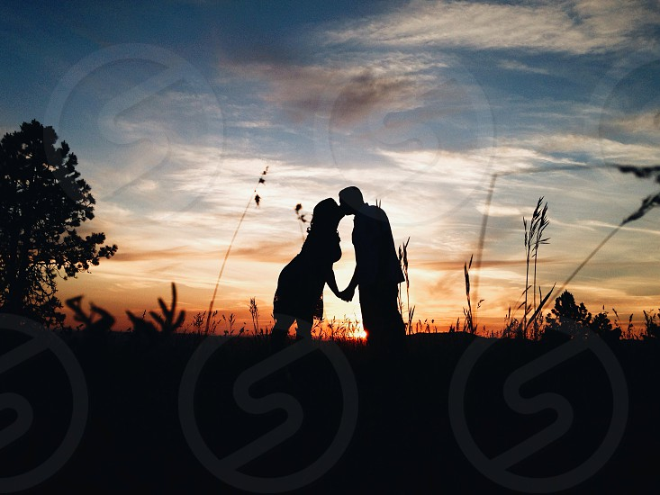 man and woman kissing on sunset view photo