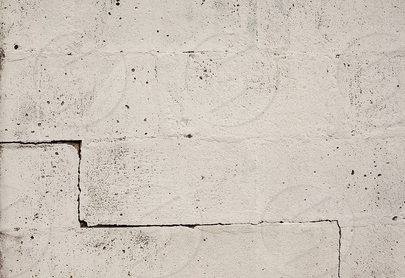 Texture of an old wall big bricks painted in white with one crack on one side. photo