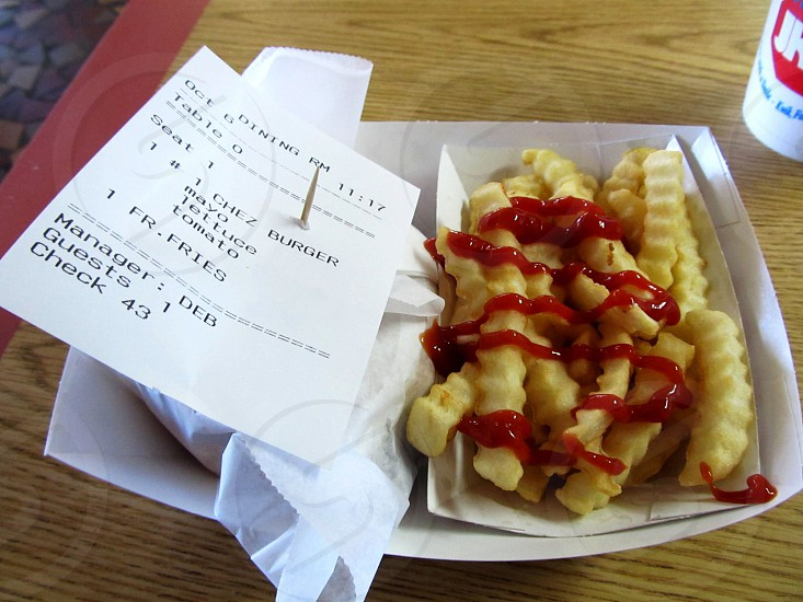 Wax paper wrapped burger with receipt and ketchup covered crinkle cut french fries photo