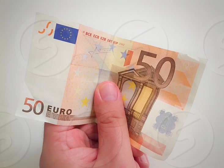 50 business euro finance hand holding money white bank cash currency paper fifty human isolated banknote bill finger give giving hold paying background buy concept exchange financial investment pay rich success businessman man payment people person saving shopping wealth bills debt male banknotes credit crisis deposit economic invest photo