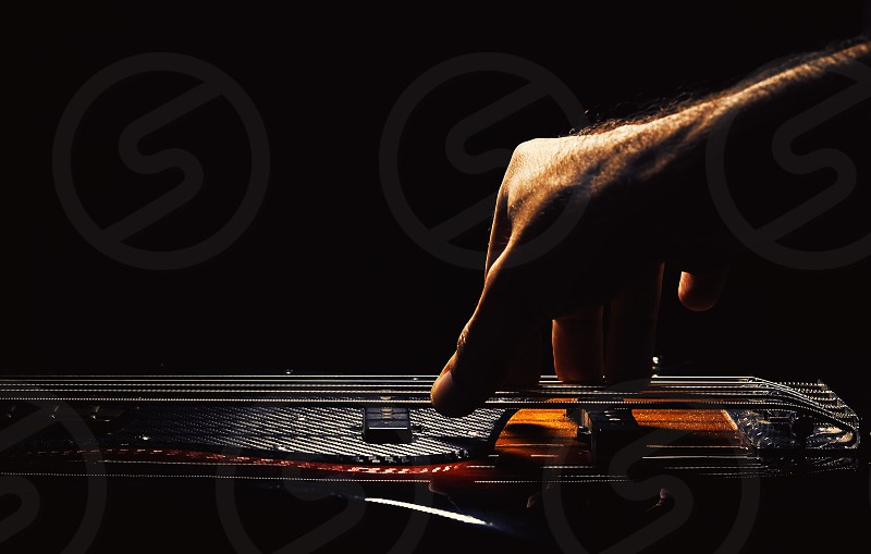Male hand playing five strings jazz bass guitar.  photo