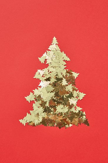 New Year decorative tree handmade from shiny small spruces on a red background copy space. Greeting holiday card. photo