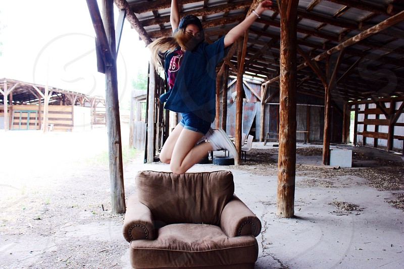 woman wearing blue printed crew neck shirt and black beanie hat jumping on a brown fabric sofa chair during daytime photo