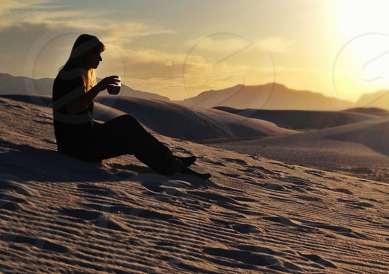 woman sitting on sand holding cup photo