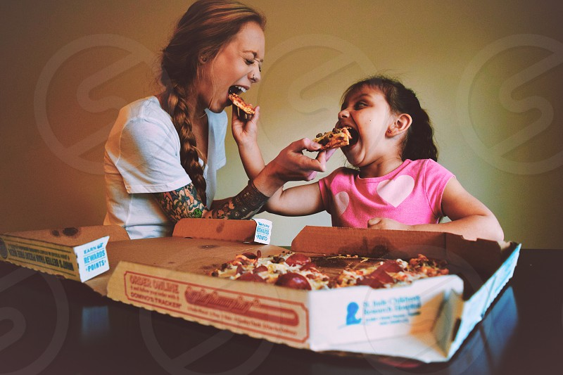 smiling woman with smiling girl feeding each other pizza photo