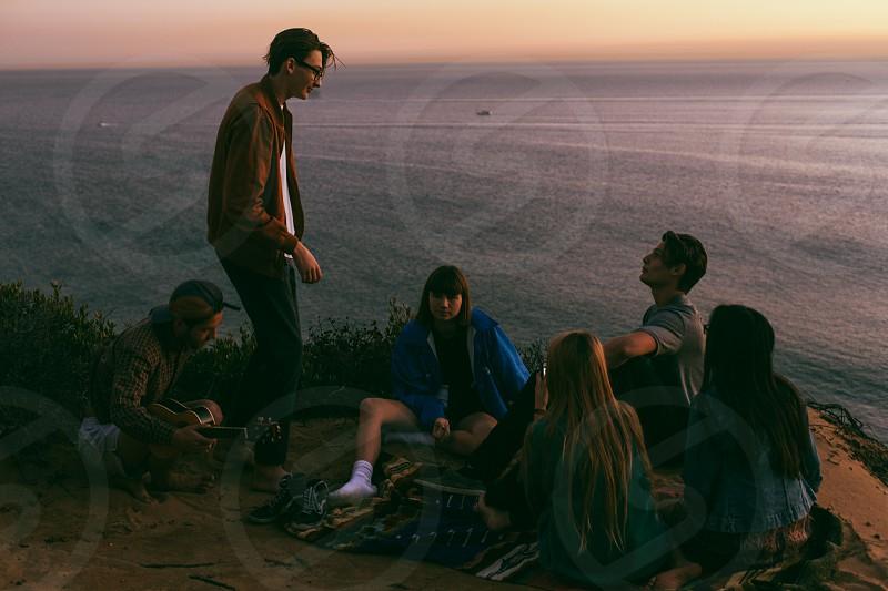 man in brown jacket standing between 5 seated people in beach photo