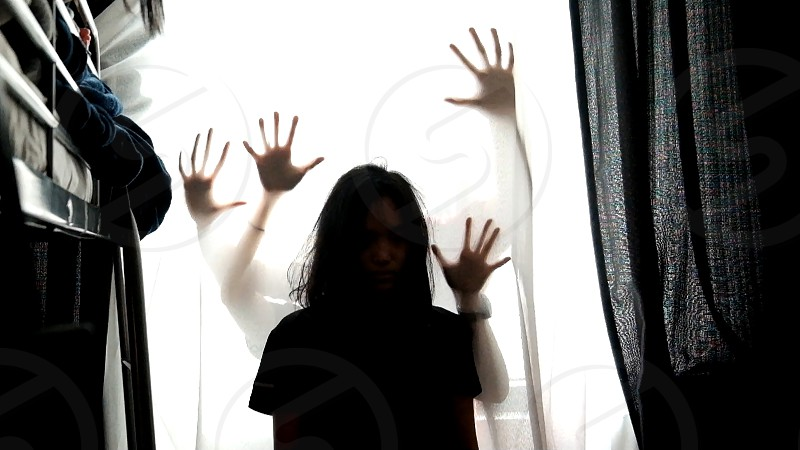 Hand silhouettes hidden in the light behind a young female surrounded by darkness photo