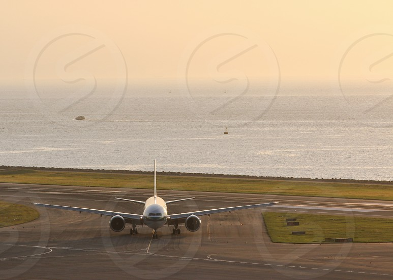 Jet airplane airliner runway ocean sunset golden.  photo