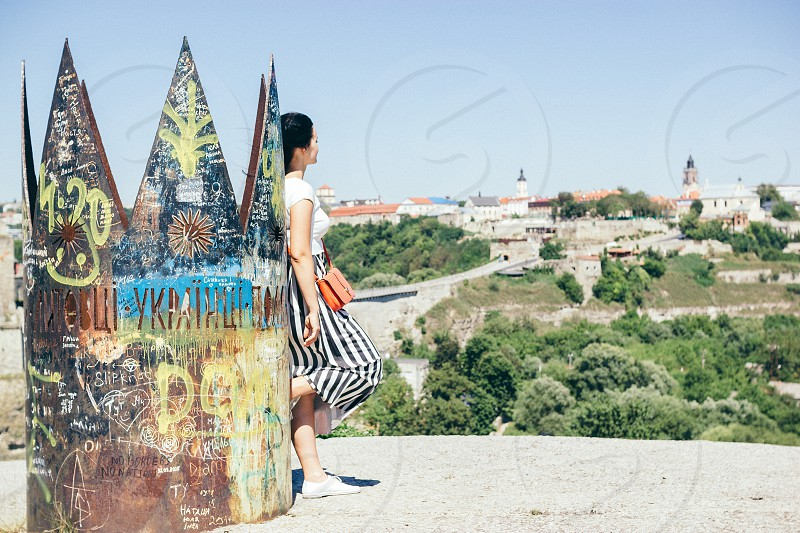 Woman standing near crown in profile and looking at the city (Ukraine Kamianets-Podilskyi) photo