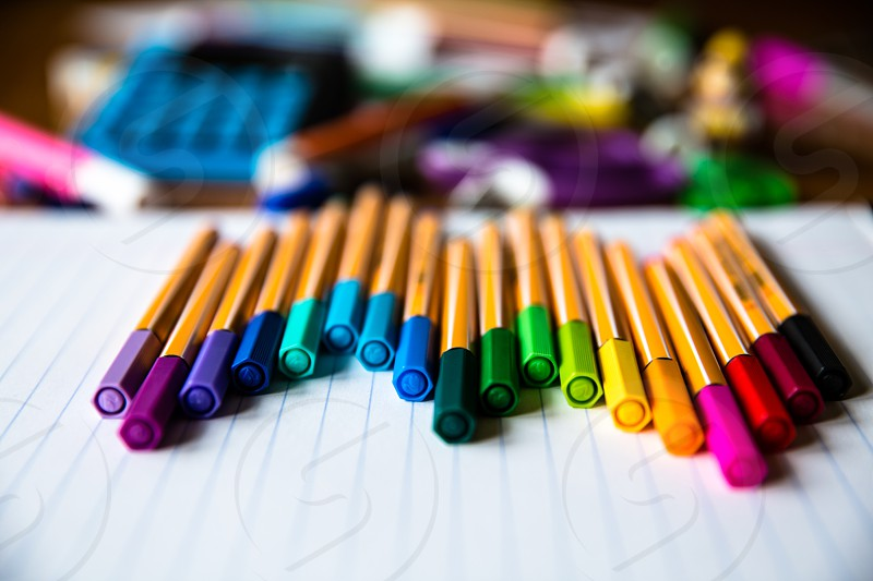 colored pencils on top of lined paper selective focus photography photo