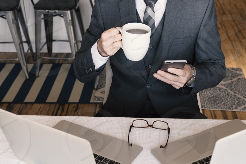 Business professional checking messages enjoying coffee with laptops and eyeglasses. photo