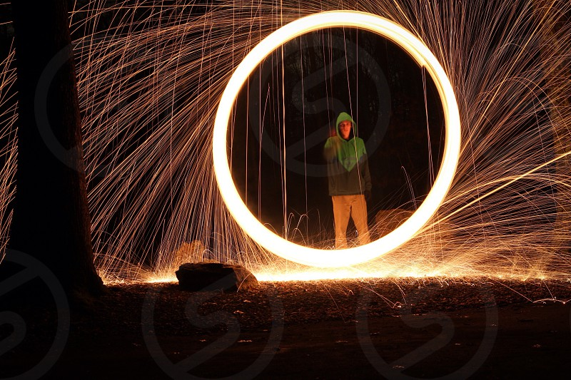 man in grey and green hoodie standing in front of circling fireworks display photo