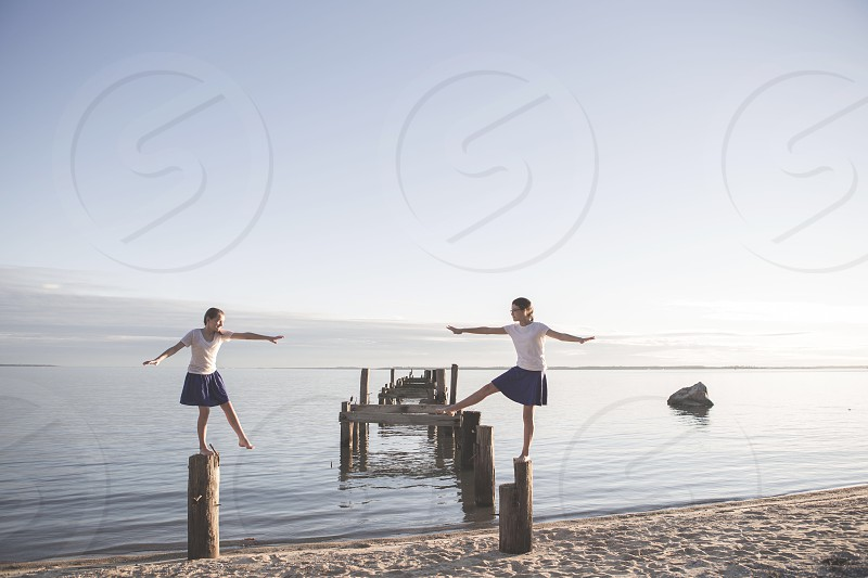 person wearing white t shirt and blue skirt one foot balancing on brown standing log beside seashore photo