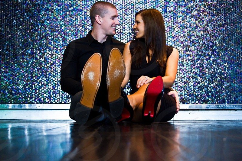 man in black formal shirt sitting on floor and smiling beside woman in black and red stiletto shoes photo