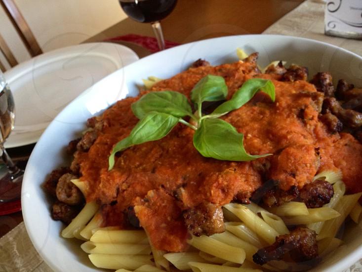 Penne pasta with marinara sausage and basil photo