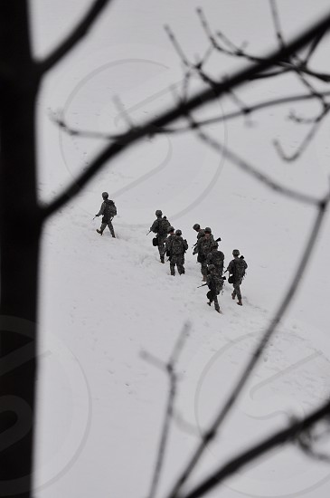 military soldiers with rifles walking a white snow covered hill photo