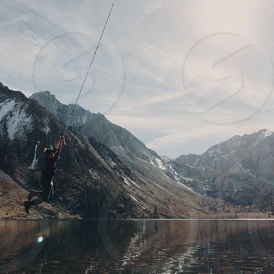 man wearing black long sleeve shirt hanging on a rope photo