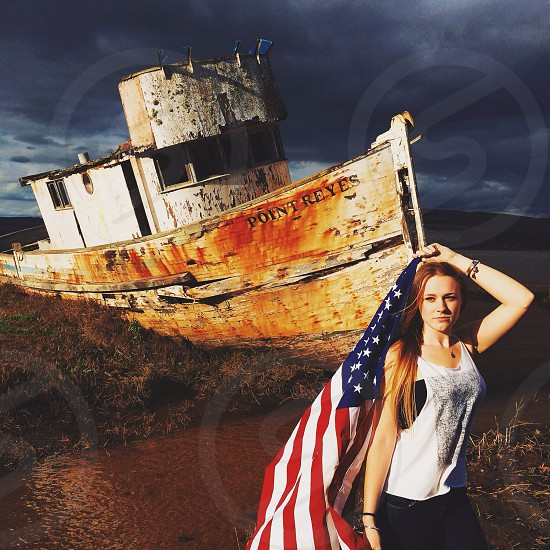 woman holding an american flag with the ship point reyes behind her photo