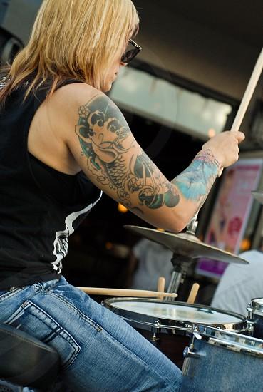 tattooed female drummer playing photo