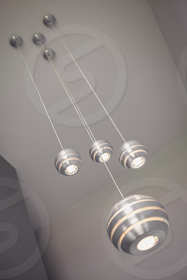 Details of a modern decorative lights metal balls hanged on high gray ceiling. photo