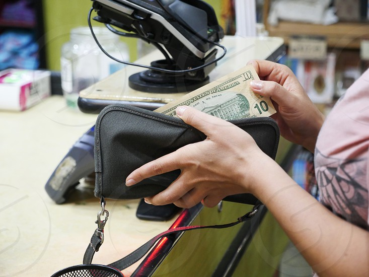 Shopper pulling  $10 bill out of her wallet at the register photo