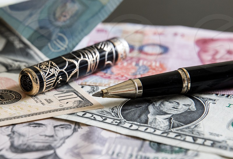 black and gray pen with one us dollar banknotes on the table photo