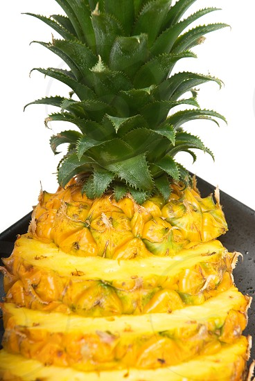 ripe vibrant pineapple sliced on a black plate photo