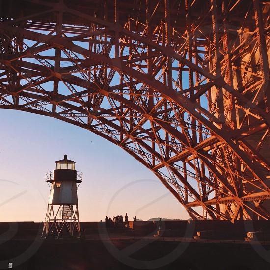 white round tower underneath red metal bridge arch photo