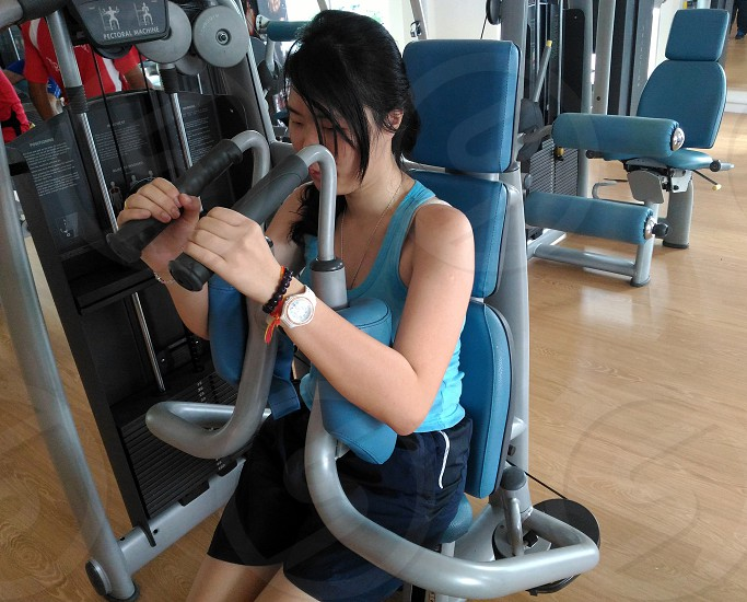 woman in blue tank top working out during daytime photo