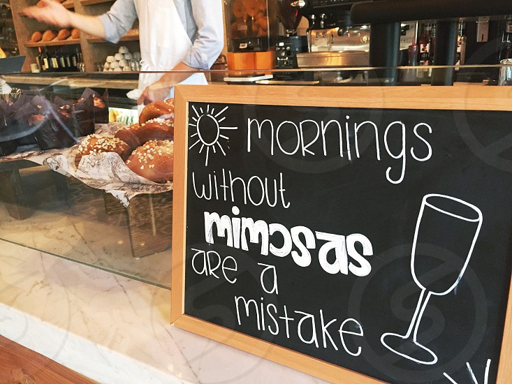morning with out mimosas are a mistake on black board near the glass display in the cafe photo