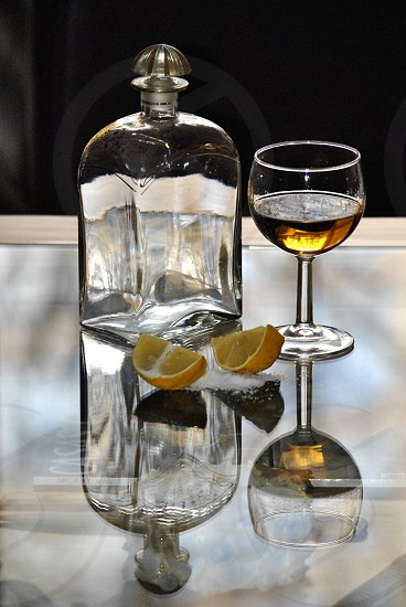drink in a wine glass next to an empty bottle 2 lemon wedges and salt photo