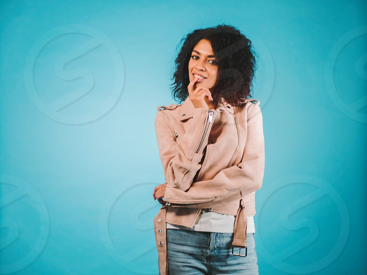Relaxed carefree smiling young woman wearing pink fashion jacket having positive cheerful expression on her face rejoicing at her leisure time. Pensive african trendy girl. photo