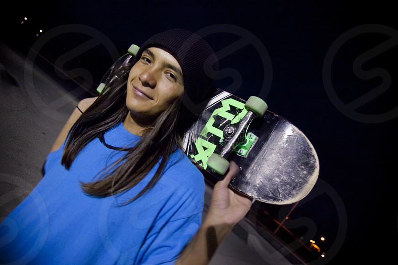 Native American teenage boy (Shoshone Bannock) rests his skateboard on the back of his shoulders while at a designated skate park located in Blackfoot Idaho photo