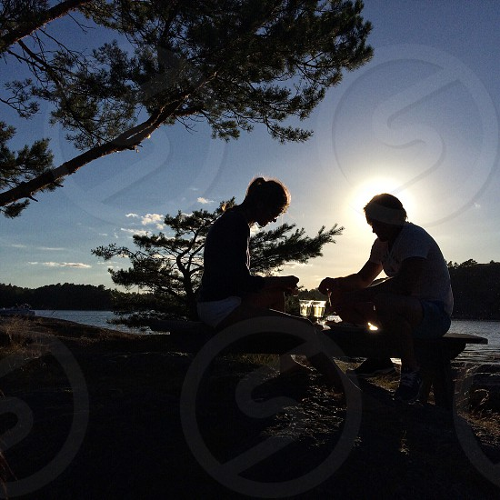 woman and man sitting on wooden chair over sunrise view photo