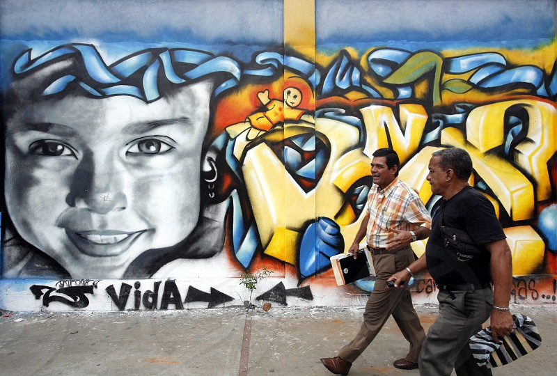 people in a street with graffiti in the city of Valencia in the west of Venezuela. photo