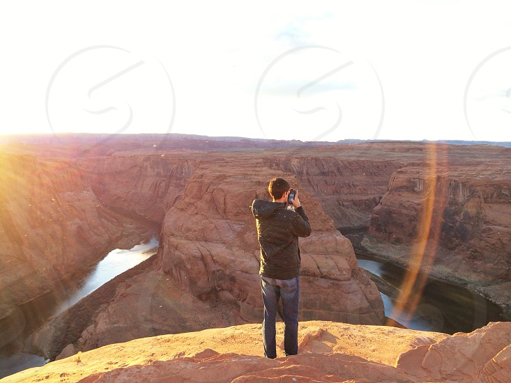man wearing a black jacket taking a picture of the grand canyon photo