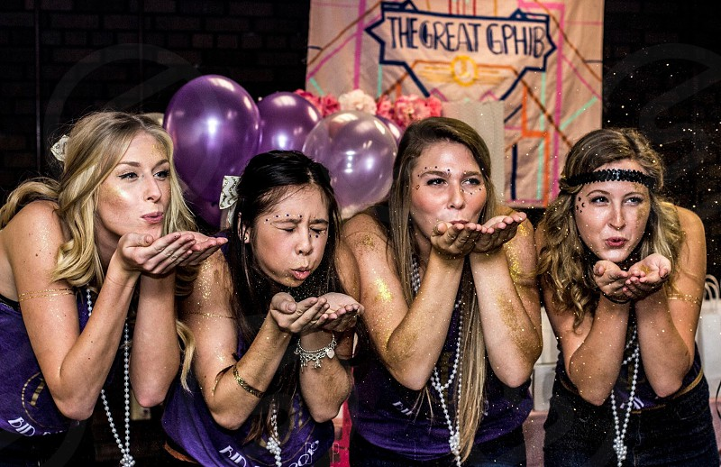 four women blowing on hands near purple balloons photo