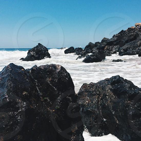 photography of body of water crashing on rocks photo