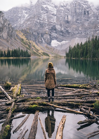 person wearing brown coat standing on floating logs on water facing snow covered rocky mountain at daytime photo