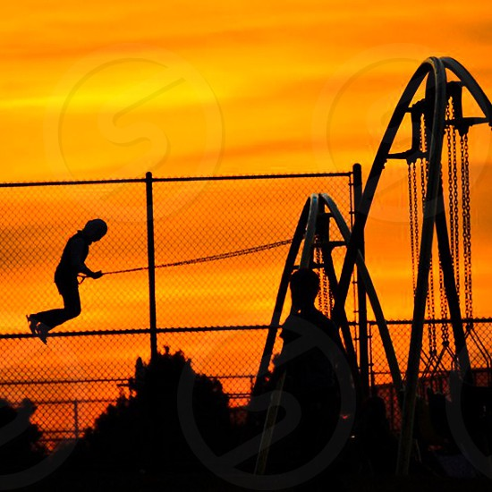 child on a swing set at sunset photo
