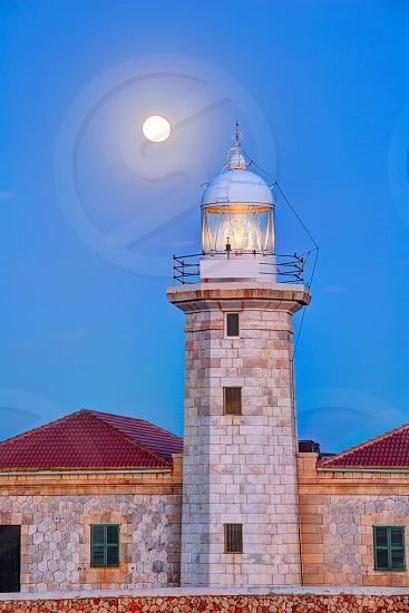 Ciutadella Menorca Punta Nati lighthouse with moon shining in sky photo