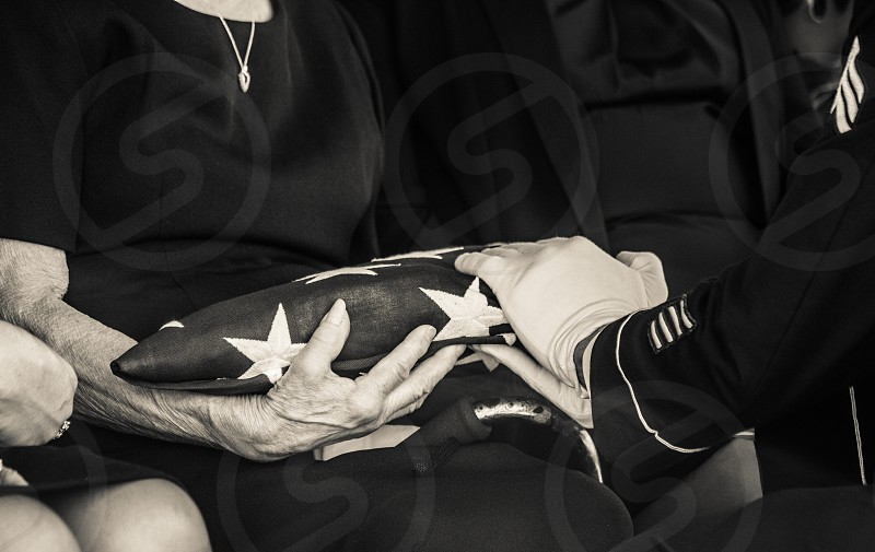 person receiving the flag of u.s.a from a soldier photo