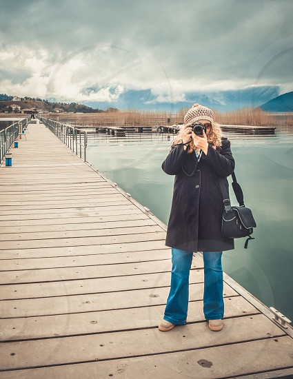 Beautiful Blonde Woman Photographer Standing On The Dock And Photographing Nature Landscape photo